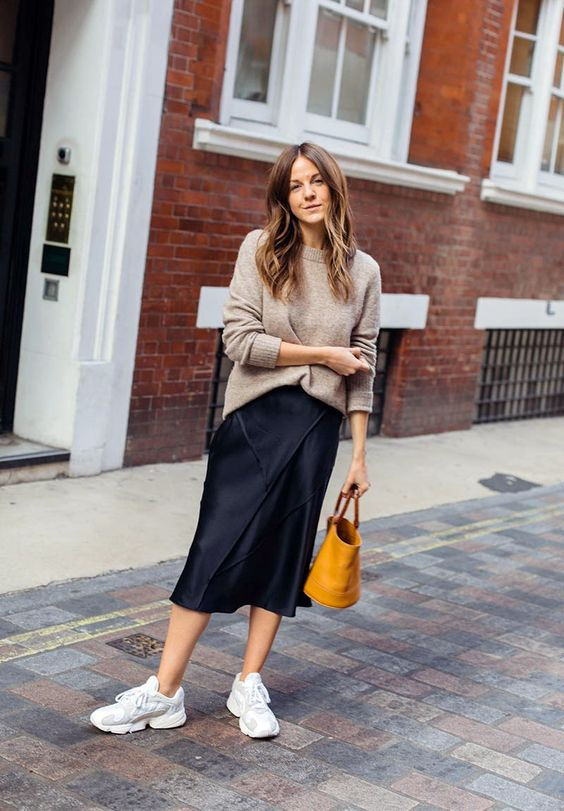 a tan jumper, a navy slip midi skirt, white dad trainers and a honey yellow bucket bag for a chic look