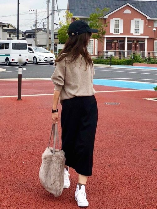 a tan sweatshirt, a black midi pencil skirt, white sneakers and a faux fur bag plus a black cap