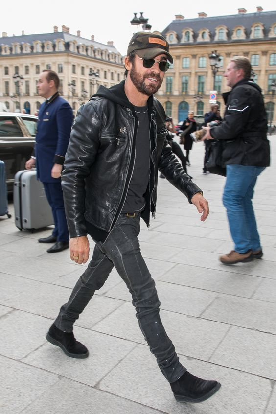 a total black look with a tee, jeans, boots, a hoodie with a zip and a leather jacket plus a baseball hat