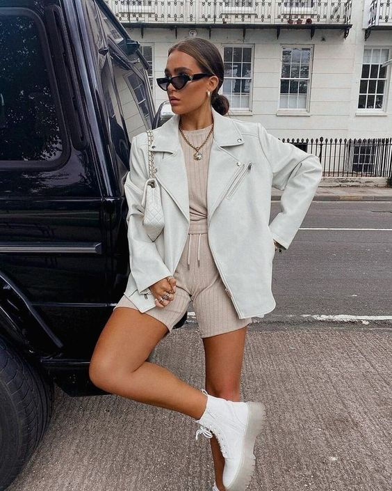 a trendy and comfy look with a tan top and shorts, white combat boots, an oversized white leather jacket and a white bag