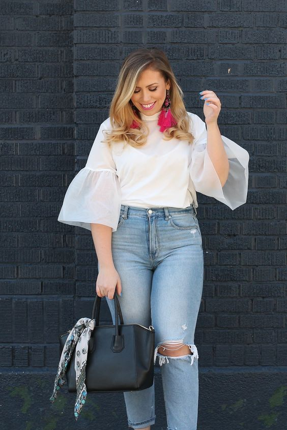 a vivacious spring look with light blue ripped moms, a white blouse with bell sleeves, bright pink earrings and a black bag