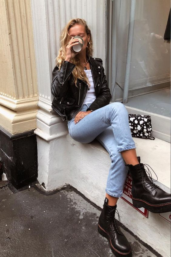 a white crop top, blue mom jeans, a black leather jacket, black combat boots and a black printed bag