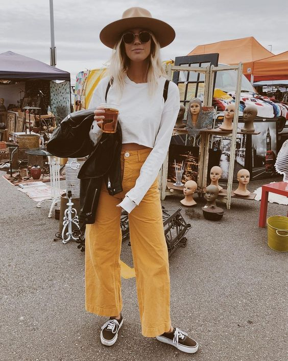 a white crop top, yellow jeans, a tan hat, a black leather jacket and black sneakers