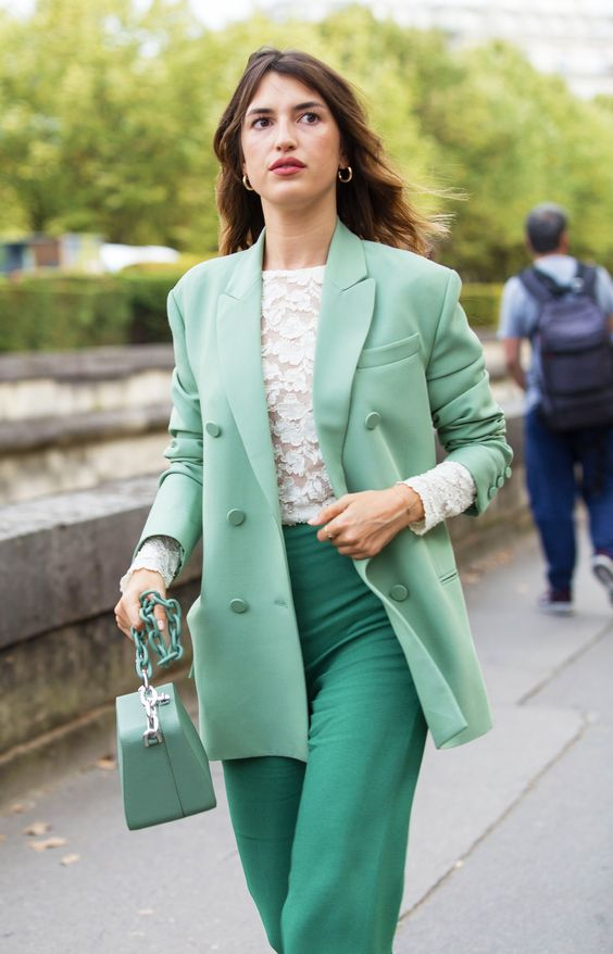 a white lace long sleeve top, an oversized light green blazer, emerald pants, a mini crossbody bag for spring