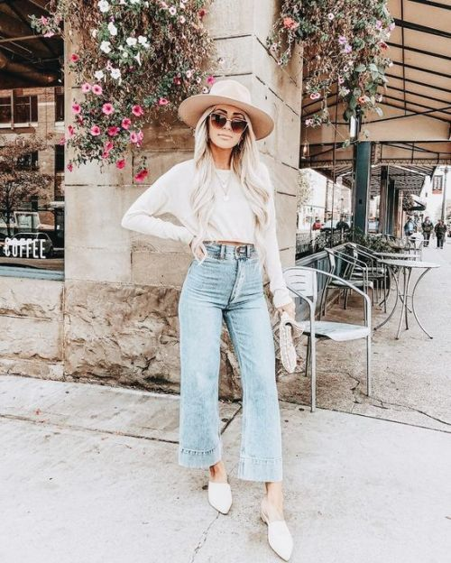 a white long sleeve crop top, blue flare jeans, white mules, a white hat and a clutch