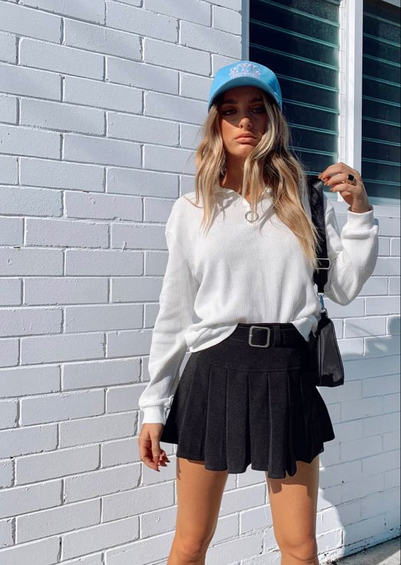 a white long sleeve polo shirt, a black pleated mini skirt, a blue baseball cap and a black bag