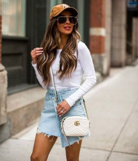 a white long sleeve top, a blue denim asymmetrical skirt, a white crossbody bag, an amber baseball hat