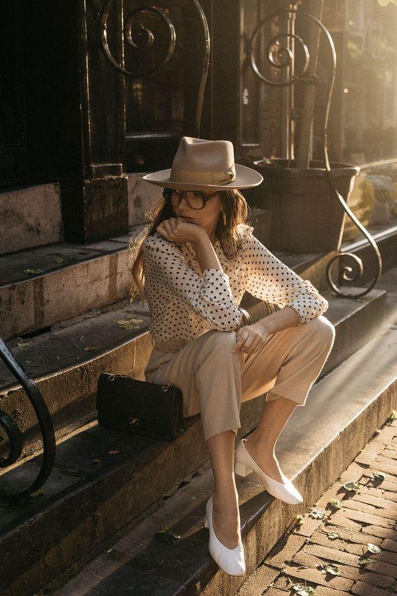 a white polka dot blouse, tan pants, white vintage shoes, a tan hat and a black crossbody bag
