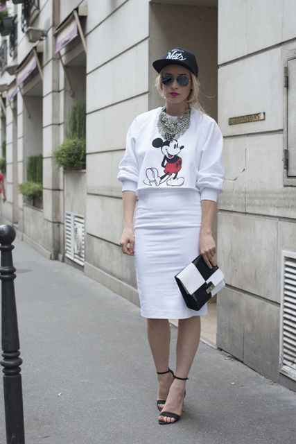 a white printed sweatshirt, a white midi pencil skirt, a statement necklace, a black baseball cap and black heels