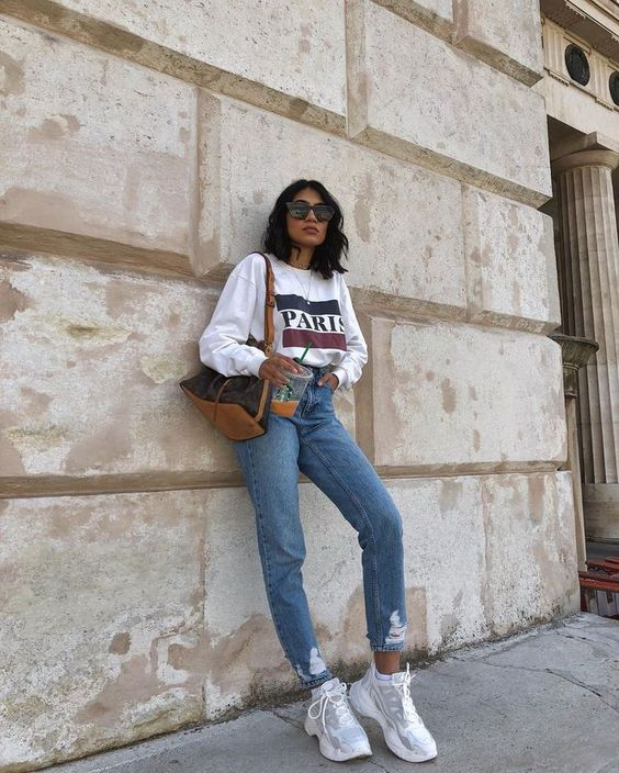 a white printed swetshirt, blue straight leg jeans, dad sneakers and a tote for every day