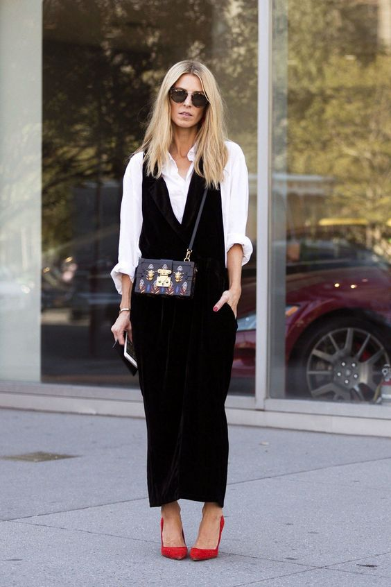 a white shirt, a black velvet slip dress with pockets, red shoes and a whimsical bag