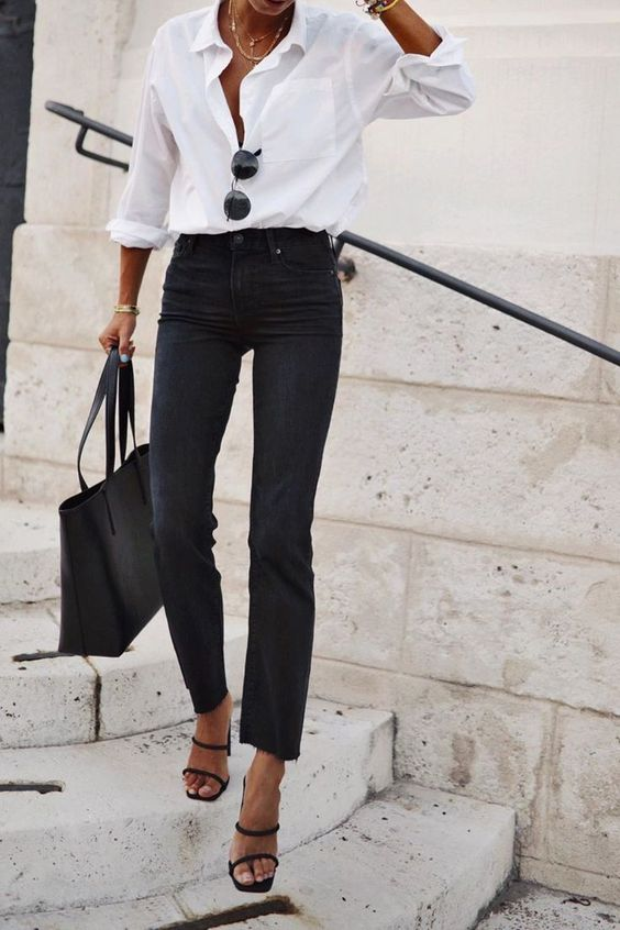 a white shirt, black jeans, a black tote and strappy heels for a chic casual look with a touch of girlish