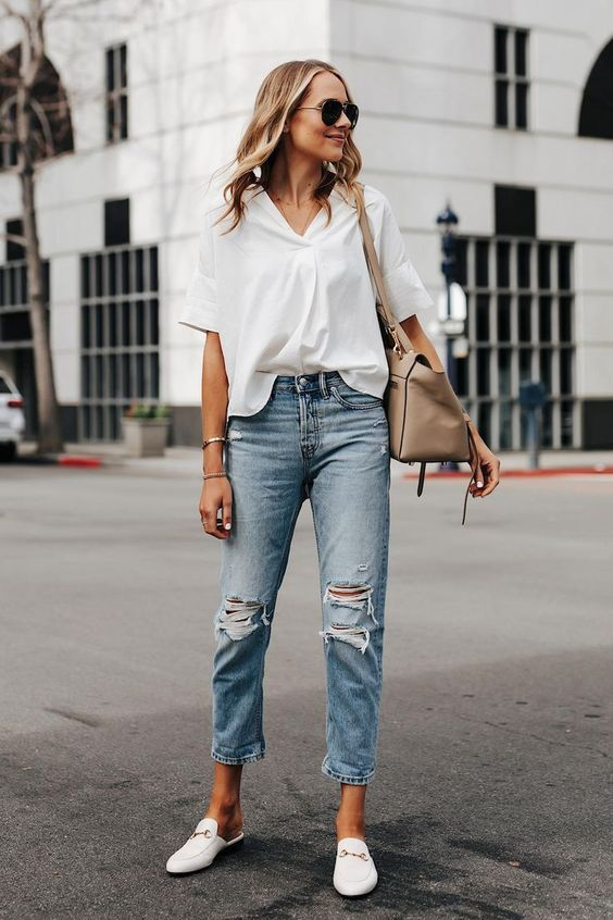 a white shirt, blue ripped boyfriend jeans, white mules, a grey bag for spring or summer