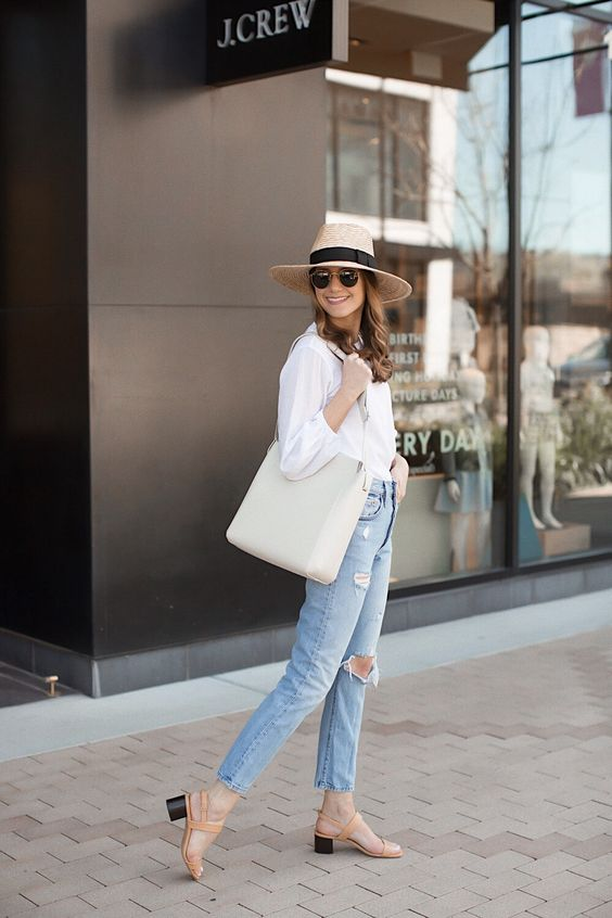 a white shirt, blue ripped jeans, nude sandals with block heels, a hat and a creamy tote