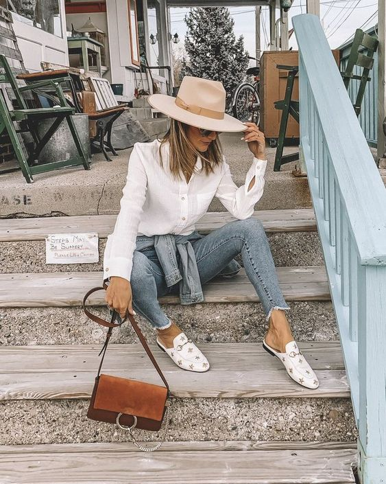 a white shirt, blue skinnies, white star print mules, a neutral fedora hat and a brown bag