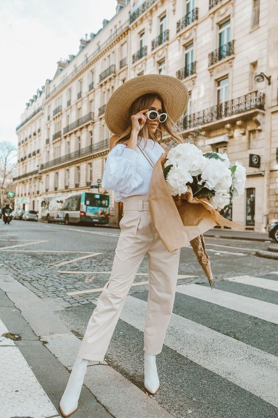 a white shirt with puff sleeves, tan trousers, white boots, a straw hat and vintage sunglasses