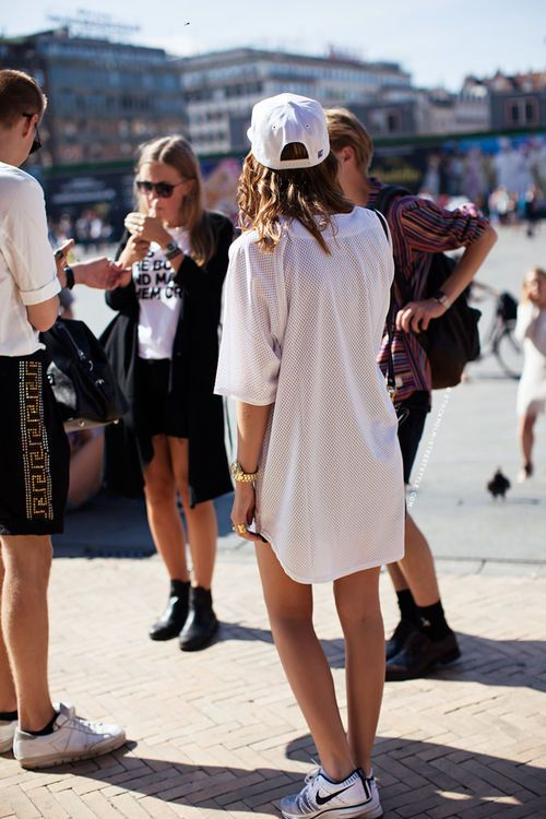 a white shirtdress, white sneakers, a white baseball hat for a comfortable sporty look