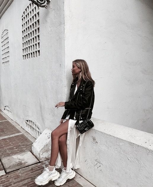 a white slip midi dress, white dad sneakers with tan socks, a black leather jacket and a black bag