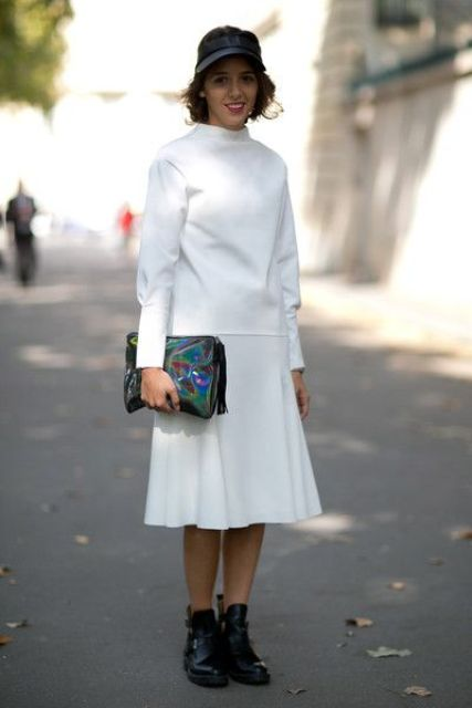 a white sweatshirt, a white pleated midi skirt, moto boots, a colorful clutch and a black baseball hat