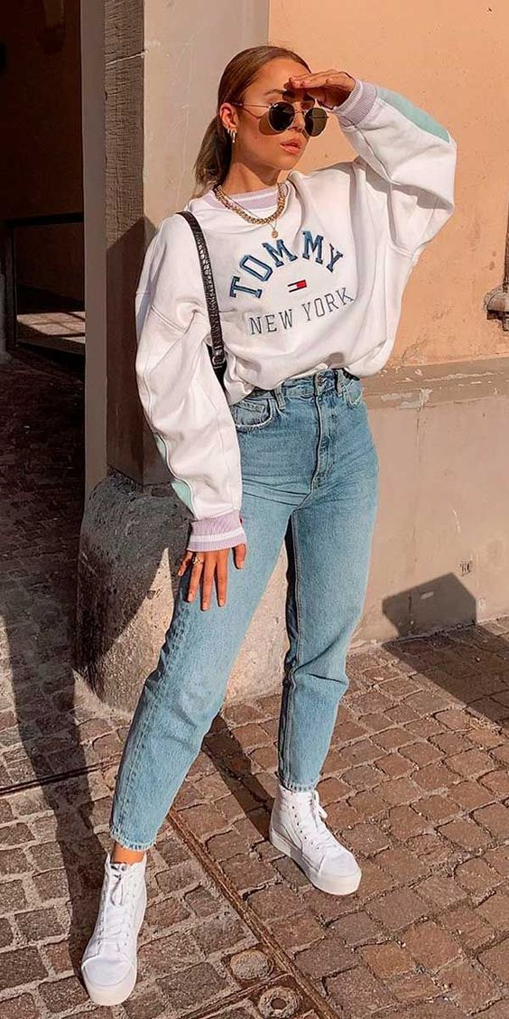 a white sweatshirt, blue mom jeans, white sneakers and a statement necklace for spring