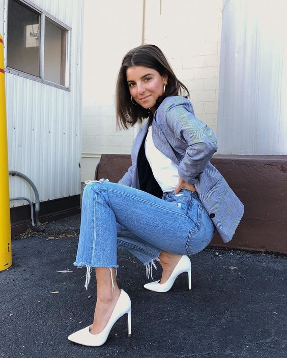 a white t-shirt, a grey plaid blazer, blue mom jeans and white pumps on high heels