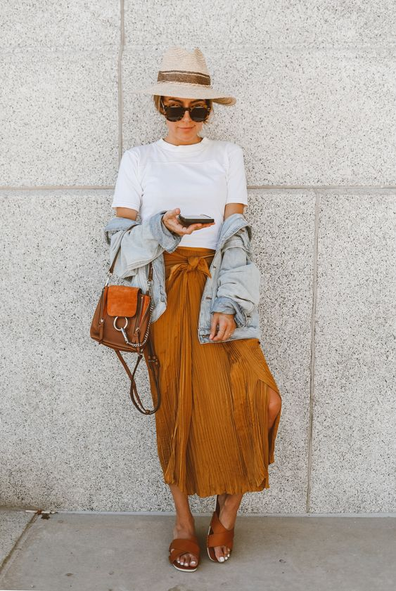 a white t-shirt, a mustard pleated midi, brown slippers, a brown bag and a denim jacket plus a hat
