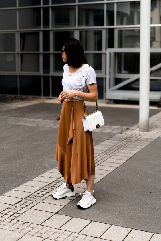 a white t shirt, a rust colored layered midi skirt, dad sneakers and a white bag for summer or spring to summer dats