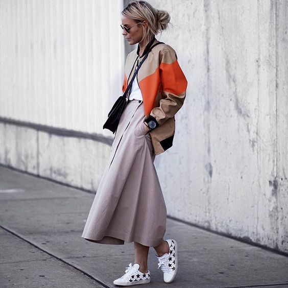 a white tee, a blush A line midi skirt, a color block bomber jacket and star printed sneakers