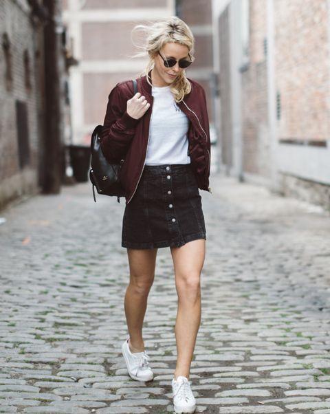 a white tee, a burgundy bomber jacket, black denim mini, white sneakers and a backpack