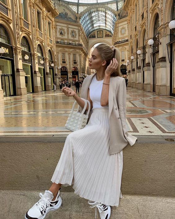 a white tee, a creamy pleated midi, a tan oversized blazer, dad sneakers and a pearly bag