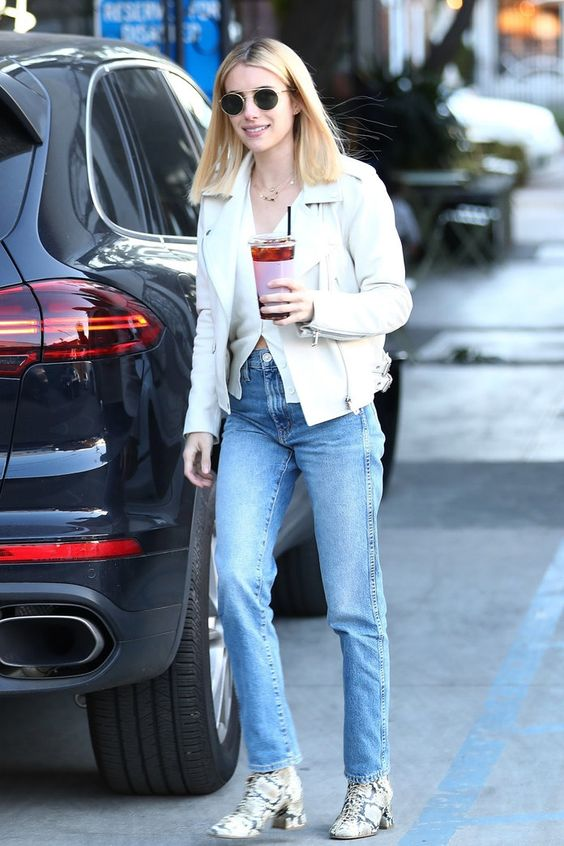 a white top, a white leather jacket, blue jeans, snakeskin print boots worn by Emma Roberts