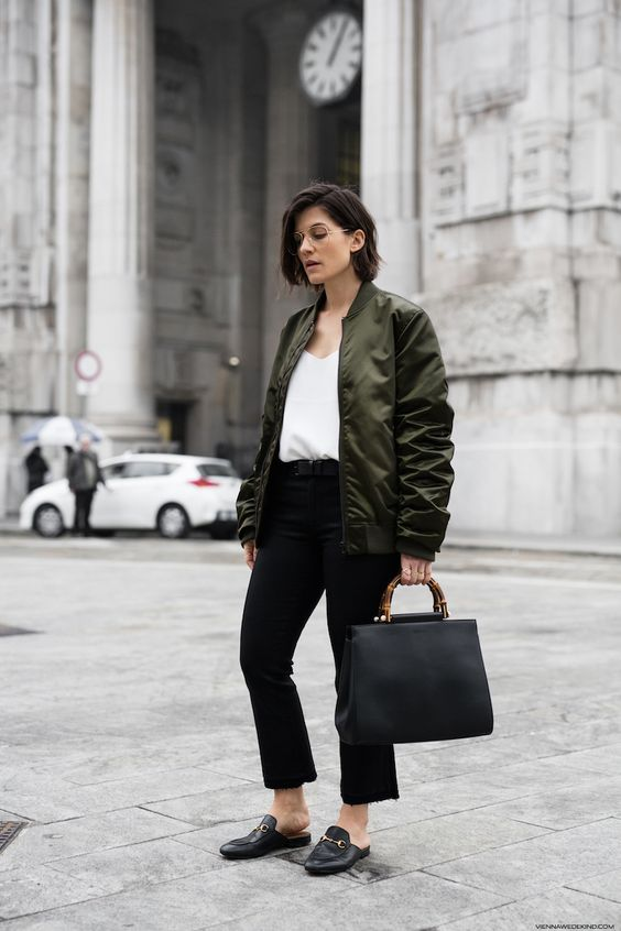 a white top, black straight leg jeans, black mules, a green bomber jacket and a black tote