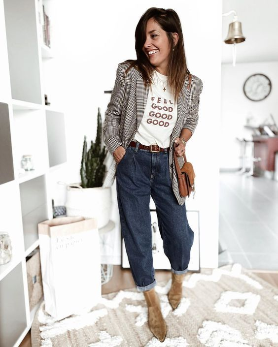 a work outfit with a printed t shirt, navy mom jeans, tan velvet booties, a plaid blazer and a brown bag