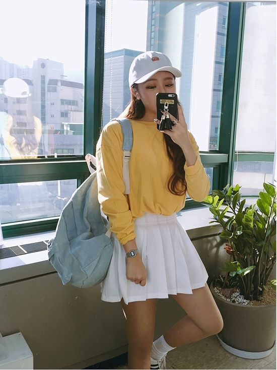 a yellow long sleeve top, a white pleated mini skirt, white sneakers, a white baseball cap and a blue backpack