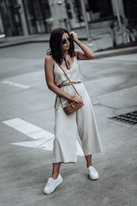 an off white jumpsuit with wideleg pants, a tan belt, white platform sneakers and a brown mini bag