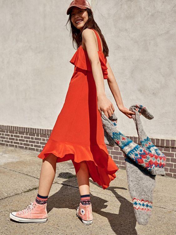 an orange A-line ruffle dress, a pink velvet baseball cap, pink velvet sneakers and printed socks