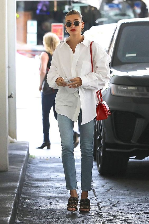 an oversized white shirt, blue jeans, strappy shoes, a red mini bag for a comfy spring look