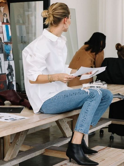 an oversized white shirt, blue skinnies, black booties with kitten heels and cool accessories for work