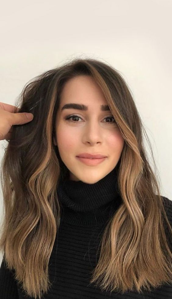 brunette hair with blonde face framing and waves looks chic and beautiful and catches all the eyes