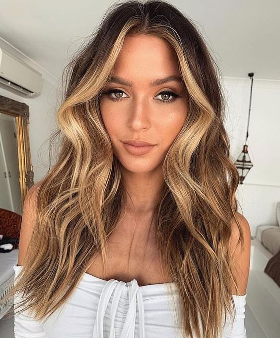 dark chestnut hair in long waves and honey blonde balayage and face-framing highlights