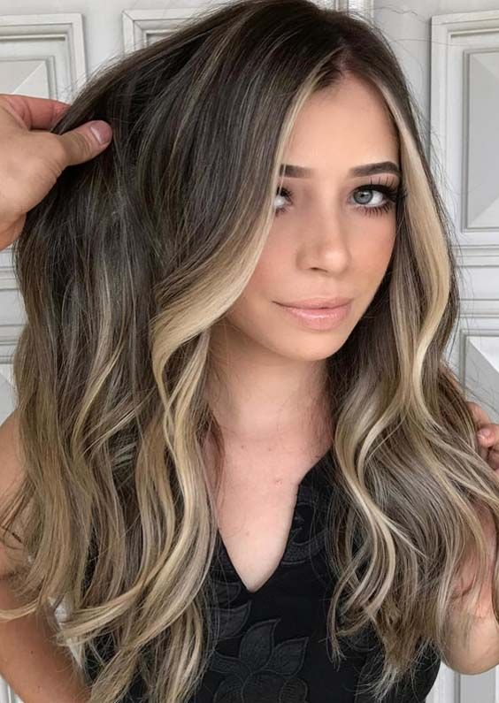 dark wavy hair with blonde face-framing ribbon highlights looks bolder and cooler and more dimensional