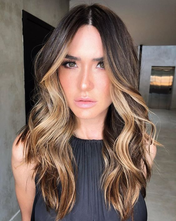 long dark waves boosted with blonde face framing highlights and balayage look catchy and bold