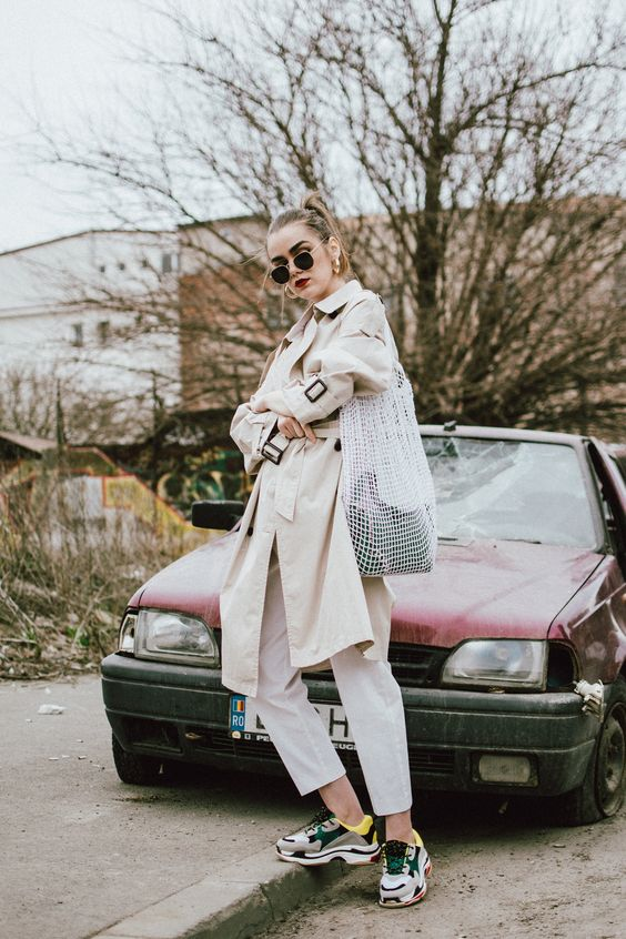 white pants, a tan trench, dad trainers and a creative bag for a super trendy spring outfit