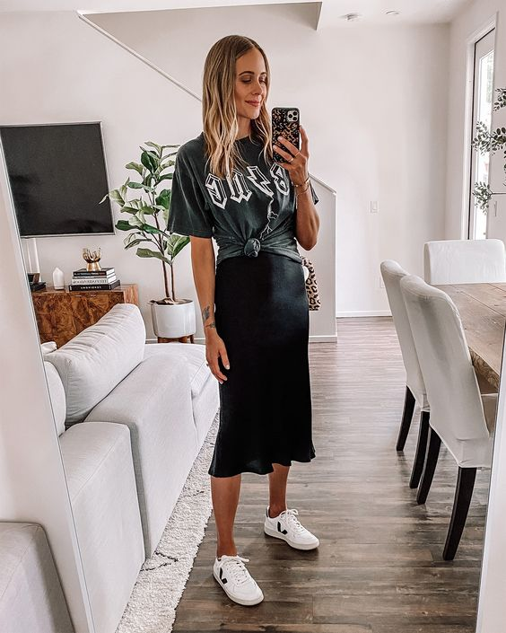 a black slip midi dress, a black printed t-shirt over it, white sneakers and a printed bag