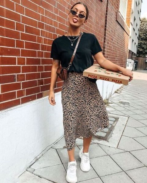 a leopard print slip midi dress, a black tied up t-shirt over it, a brown bag and white trainers for summer