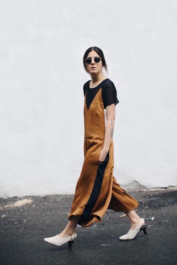 a black t-shirt, a rust-colored midi slip dress, white slingbacks for a vintage look