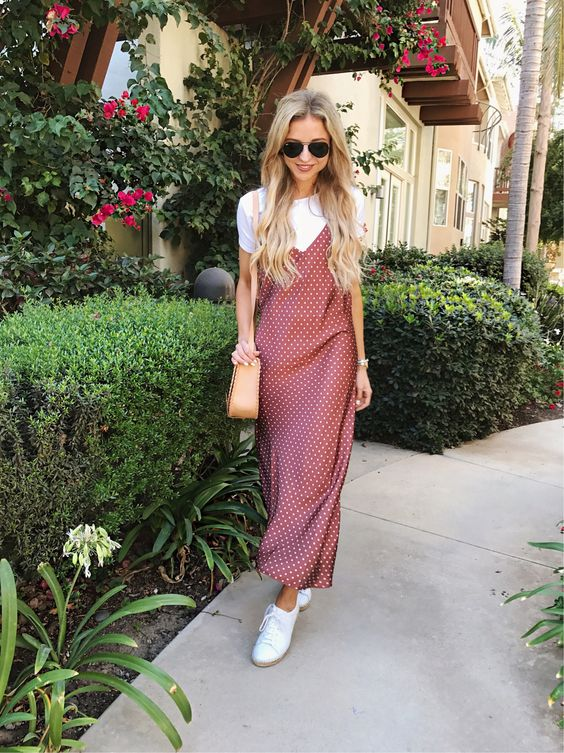 a sweet look with a white tee, a mauve polka dot maxi slip dress, white sneakers and a tan bag