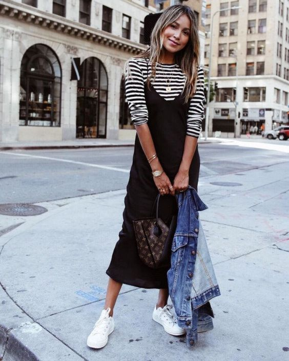 a striped black and white t-shirt, a black slip midi dress, white sneakers, a blue denim jacket and a brown bag