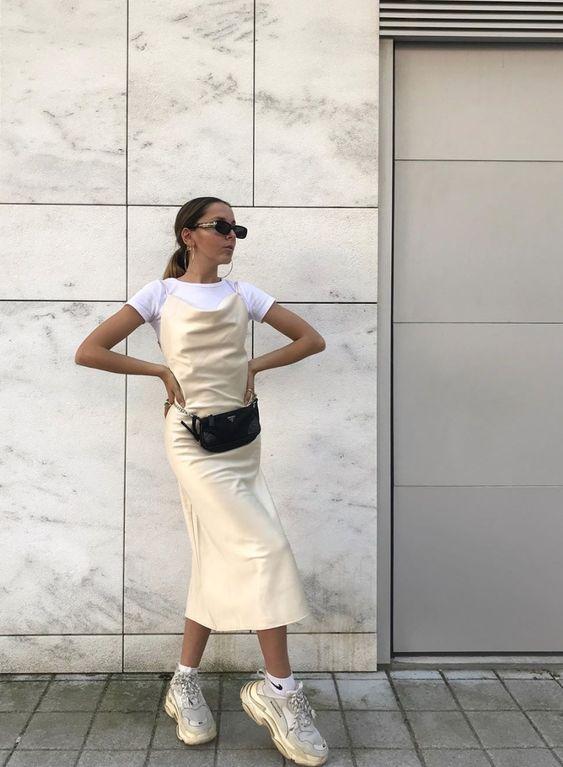 a white t-shirt, a creamy slip midi dress, neutral trainers and white socks plus a black waist bag