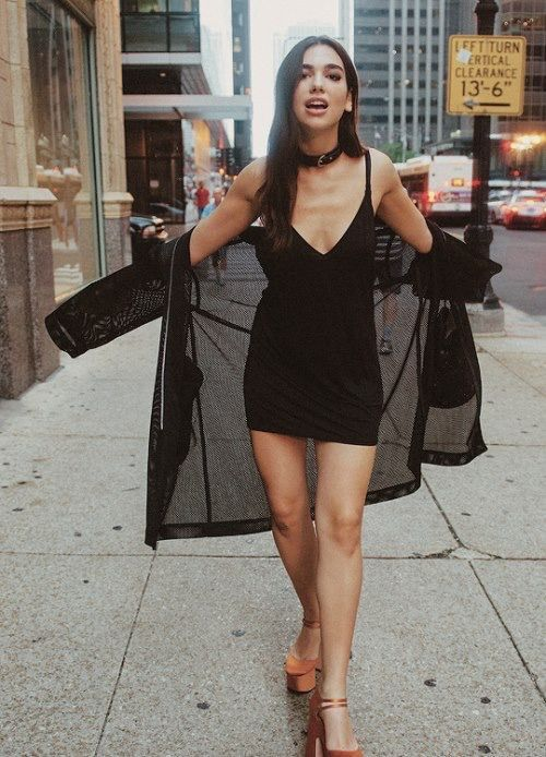 Dua Lipa wearing a black slip mini dress, a choker, rust-colored platform heels and a black duster